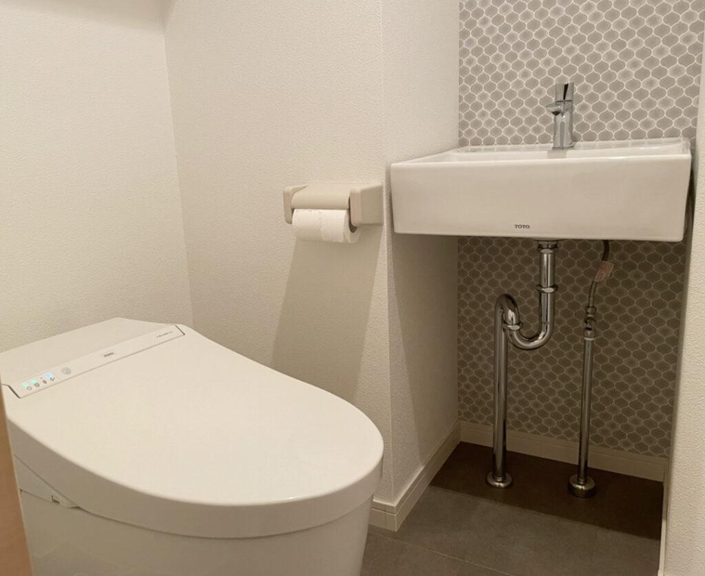 節水性のあるタンクレストイレをセレクト。<br /> 壁の凹凸にジャストサイズの手洗い器を取付けいたしました。<br /> セレクトされたクロスのお陰で、トイレ空間がより一層素敵になりました。<br />