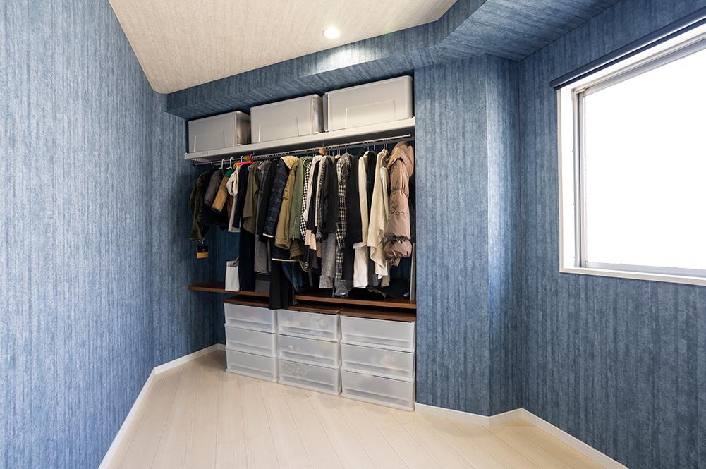洋室の一部にファミリークローゼットを作りました。<br /> 壁一面にポールを設置し、アウターやジャケットなど収納できます。<br /> 広さがあるので、棚や収納BOXを置けば、まだまだ収納力は上がります。<br /> この部屋のクロスは全面ネイビーで、いつもいる場所はシンプルに、収納場所は遊び心のあるセレクトです。