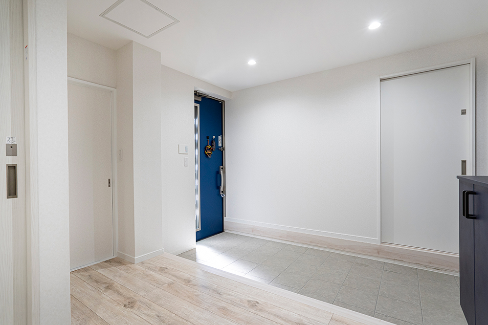 店舗の裏口だった部分を玄関にしました。広い玄関を挟んで、奥は洋室へ。手前は2階へと続く階段です