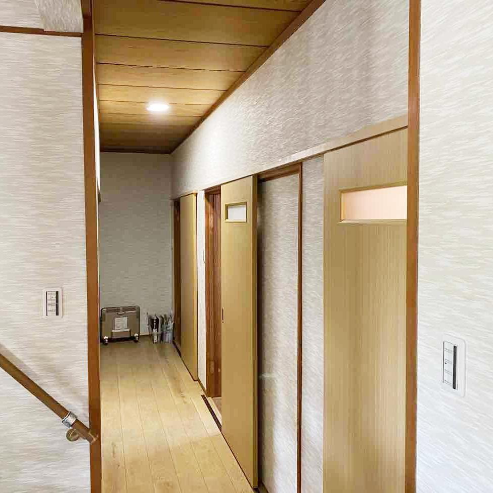 玄関同様の織り柄のクロスと明るい色の床で、廊下の印象もガラリと変わりました。