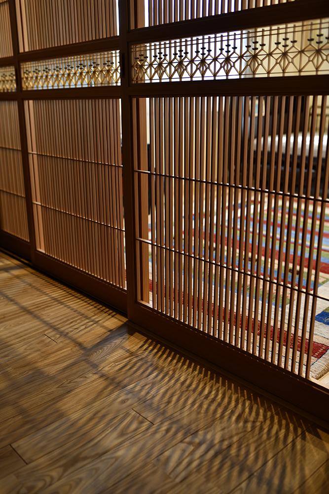2部屋を仕切る3枚の建具は、大川の組子職人 仁田原さんと打ち合わせを重ねて制作されたオリジナル。<br /> 組子の影が無垢の床材に浮かび上がり、幻想的な雰囲気に。