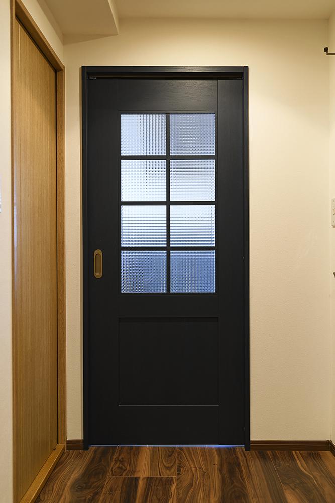 LDKの入口は、ブラックオークにチェッカーガラスの扉。<br /> ヴィンテージテイストの室内のアクセントになっています。