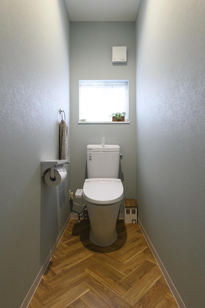 ブルーグレーの壁と、ヘリンボーンの床で仕上げた、ナチュラルなトイレ空間