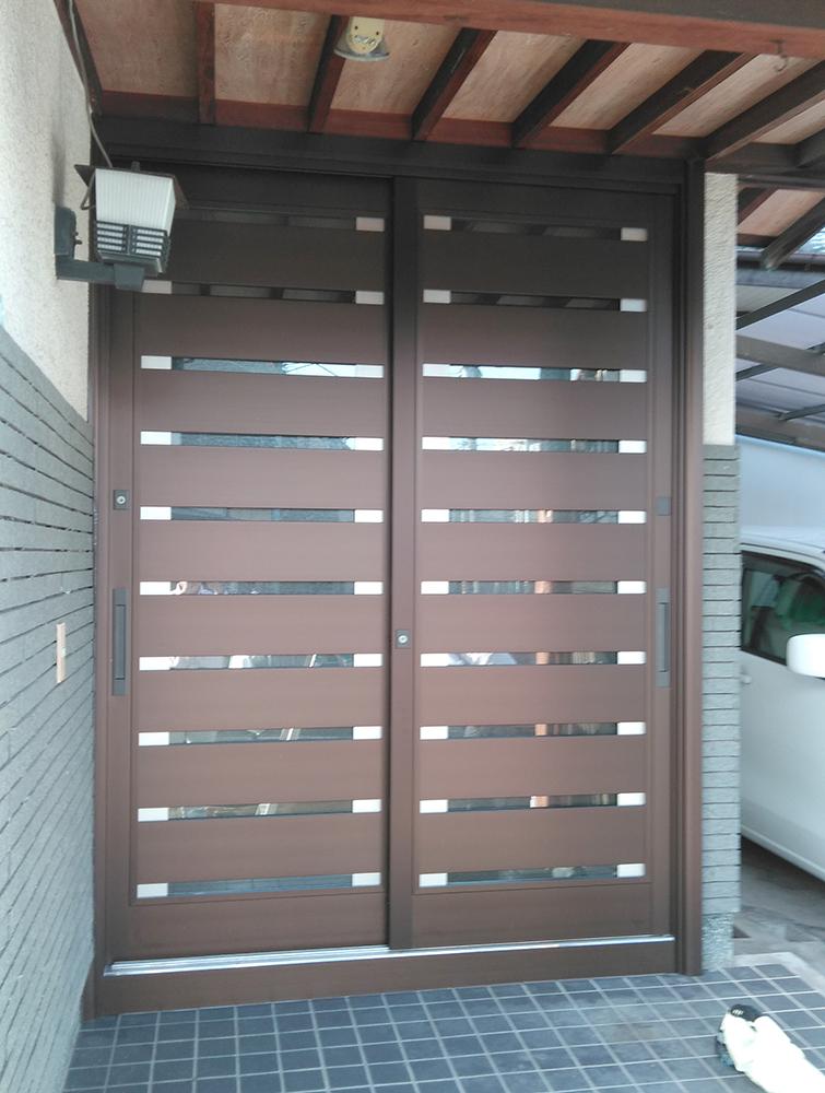 既存の枠に新しい引戸枠をかぶせて取付けるカバー工法。<br />壁を壊さず、最新の玄関引戸へリフォームできます。<br />横格子のデザインで、モダンな印象になりました。