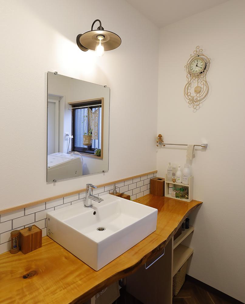 リフォーム後の洗面所<br /> 造作カウンターの木材は、折れ戸として使われていた板を再利用しました。<br /> 洗面ボウルとの相性も良く、味わいある空間になりました。<br />